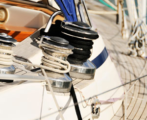 Deck of a sailboat, closeup of ropes tied to winch.